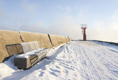 Beacon and bench on snowy mole royalty free stock photo