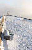 Beacon and bench on snowy mole Royalty Free Stock Photo