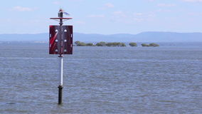 Beacon With Boat. Two speed boats pass behind a red beacon on open water stock footage