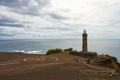 Beacon Capelinhos on the shore of Atlantic ocean, island Faial, Royalty Free Stock Photo