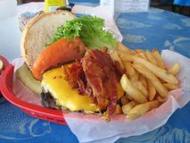 Beacon Cheese Burger. Shot of a hamburger with cheese, bacon, tomato, lettuce, and french fries royalty free stock photos