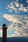 Beacon on cloudy blue sky background. Sunset on Baltic sea Stock Photo