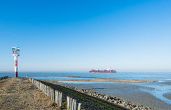 Beacon at the end of a pier. A large container ship is sailing in a Dutch estuary. A red and white colored beacon alerts on the pier Royalty Free Stock Photos