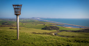 Beacon on a hill overlooking Abbotsbury Priory. Chesil Beach and The Fleet can be seen between Portland and Weymouth in the distance and St Catherine's Chapel Stock Photo