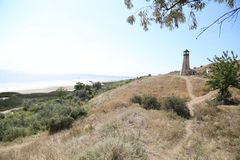 The beacon on a hillock. Green trees ahead. A view from the mountain at the sea.  stock image