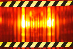 Beacon light with barrier tape. Building lot background with macro detail of an orange beacon light with two barrier tapes Stock Photography