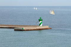 Beacon on pier and sailing yachts in sea. Barcelona, Spain; 20-11-2016 Stock Photo