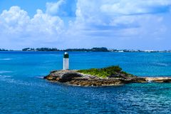 Beacon on Rocks Over blue Water. A small beacon on a small island in the bay on Bermuda Royalty Free Stock Image