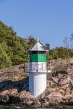 Beacon on the rocky coast of Sweden Stock Photos