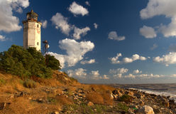 Beacon sea coast. Old vintage beacon lighthouse at the sea cost with stones and dry plant by a summer day with a blue sky and clouds as a background Stock Photos