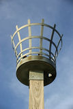 Beacon. To be used with either a fire, gas or electric light. Metal basket construction. On a wooden post. Background of blue sky with white cloud Royalty Free Stock Images