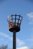 Beacon. To be used with a fire. Outer metal basket construction with an inner basket for the fire. Metalwork rusted. On a wooden post. Background of blue sky Stock Image
