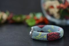 Bead crochet bracelet gray color with flower print. Close up Stock Photos