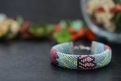 Bead crochet bracelet gray color with flower print. Close up Royalty Free Stock Photography