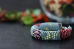 Bead crochet bracelet gray color with flower print. Close up Royalty Free Stock Photos