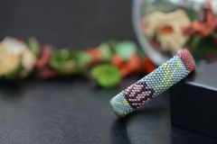 Bead crochet bracelet gray color with flower print. Close up Royalty Free Stock Image