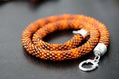 Bead crochet necklace amber color on a dark background. Close up stock photos