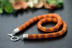 Bead crochet necklace amber color on a dark background. Close up stock photography