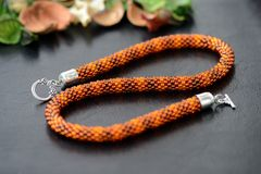 Bead crochet necklace amber color on a dark background. Close up stock image
