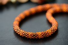 Bead crochet necklace amber color on a dark background. Close up royalty free stock photo