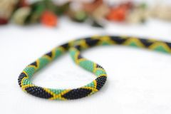 Bead crochet necklace in colors of Jamaican flag. Close up stock photos