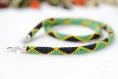 Bead crochet necklace in colors of Jamaican flag. Close up stock photo