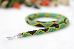 Bead crochet necklace in colors of Jamaican flag. Close up royalty free stock photos