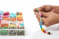 Bead jewelry. Hand holding bead jewelry over a white background royalty free stock photos