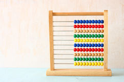 Beaded Abacus over wooden textured background. Royalty Free Stock Photos