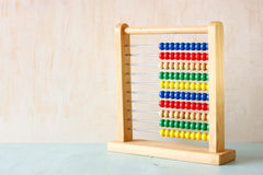 Beaded Abacus over wooden textured background. Royalty Free Stock Photography