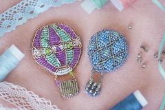 Beaded brooches in the shape of montgolfiers or balloons with silver, light blue, grey, green and violet beads and bugle surrounde. D with ribbons, lace and Stock Image