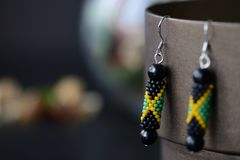 Beaded earrings in the colors of Jamaican flag on a dark background. Close up stock photography