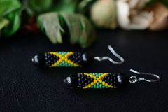 Beaded earrings in the colors of Jamaican flag on a dark background. Close up stock photo