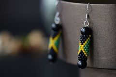 Beaded earrings in the colors of Jamaican flag on a dark background. Close up stock photos