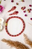 Beaded necklace and brooch set. Red garnet soutache jewelry on the white wooden background. Women accessories.  royalty free stock image