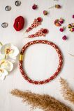 Beaded necklace and brooch set. Red garnet soutache jewelry on the white wooden background. Women accessories.  royalty free stock photo