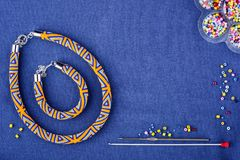 Beaded necklace of colored beads on a blue background. Copy space stock photography