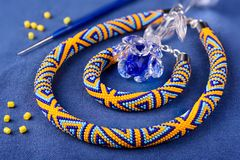 Beaded necklace of colored beads on a blue background. Beaded necklace of colored beads on a blue background stock photo