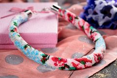 Beaded necklace with gift wrapping. Beaded necklace with gift wrapping stock photo