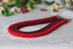Beaded necklace of red color from three ropes Stock Photo