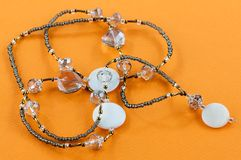 Beaded necklace with stones. Close up of beaded necklace with stones and crystals on orange stock photography