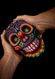 Beaded skull with hands - surprised expression. Colorful skull from mexican traditional huichol bead art, symbol of the day of the dead Royalty Free Stock Photo