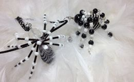 Beaded Spider Pendants. Handmade beaded spider pendants in black and white with white feather background Stock Photos