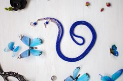 Beaded tie necklace. Blue jewelry on the white wooden background. Women accessories royalty free stock photos