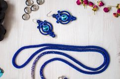 Beaded tie necklace. Blue jewelry on the white wooden background. Women accessories stock photography