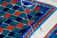 Beading. A blue and red beaded pattern sewn with a needle and thread. Close-up Royalty Free Stock Photos