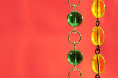 Beads. Green and yellow beads on red background Stock Image