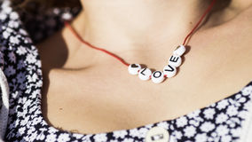 Beads around a female neck spelling the word Love Royalty Free Stock Photography