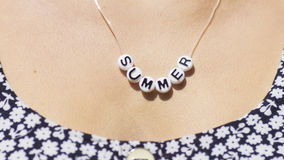 Beads around a female neck spelling the word Summer Stock Image