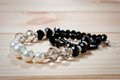 Beads of black and white pearls on a wooden background stock photos